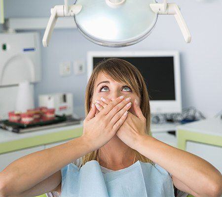 Fearful woman in need of sedation covering smile