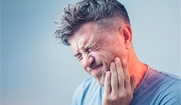 Man with severe jaw pain in need of restorative dentistry