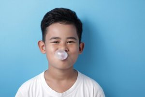 child blowing a bubble with chewing gum